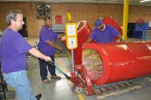 Delivery personnel from Queen Transportation unload the exhibits from Health Adventure of Asheville in a storage facility provided by Classic Leather.